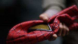 man taking off spiderman mask